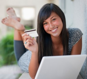 Teen using credit card and laptop