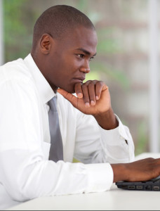 thoughtful african businessman working on laptop
